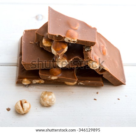 milk chocolate with nuts on a wooden background