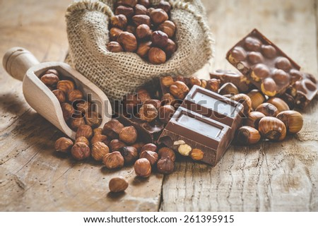 Milk chocolate with nuts on a wooden spoon in a country style. - stock photo