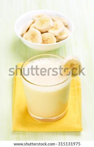 Milk cocktail with banana in glass on yellow napkin - stock photo
