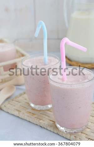 Milk coctails in glass on rustic wooden table - stock photo