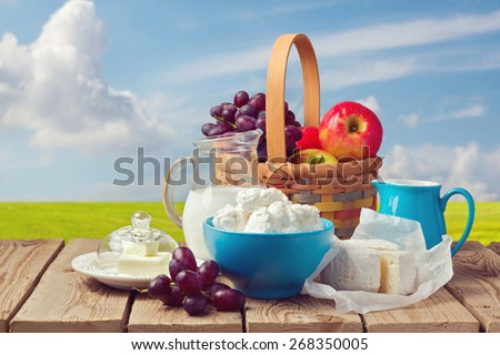 Milk, cottage cheese, butter and fruit basket over meadow background. Jewish holiday Shavuot celebration - stock photo