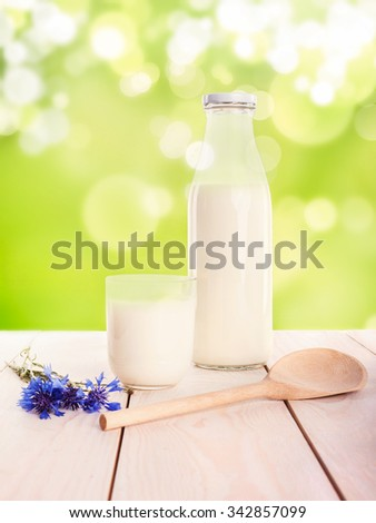 Milk cup and bottle on wooden table on green blure background
