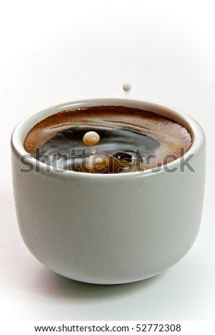 milk drop into coffee cup - stock photo