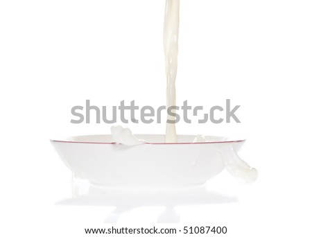 Milk falling into a bowl with reflections on the floor