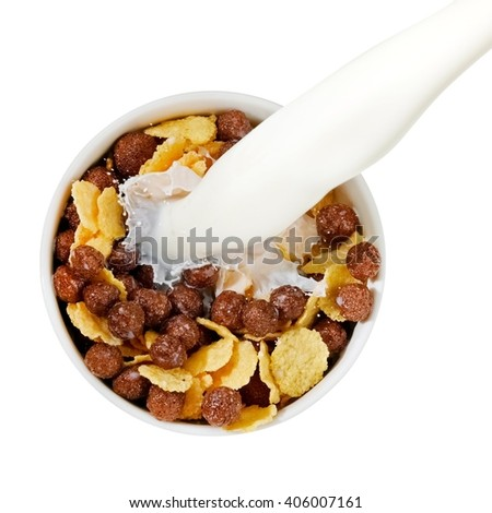 Milk flow over a cup with cornflakes and chocolate balls, top view - stock photo