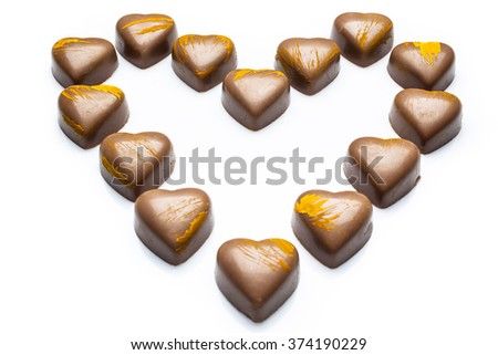 Milk heart shaped chocolates with yellow embellishment arranged in heart on white background from high angle