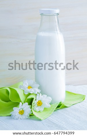 Milk in a bottle on a white wooden table