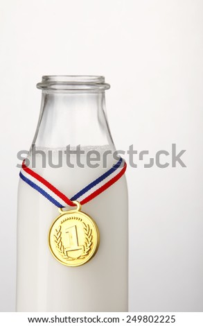 milk in a bottle with golden trophy  - stock photo