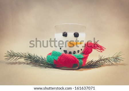 Milk in a glass, a bit of water color paint, pine as arms and we have a Milky Snowman. Ideal for Marry Christmas Card. - stock photo