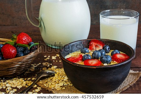Milk in a jug and oatmeal porridge with glass of milk in a pottery bowl with fresh ripe berries in a wicker bowl standing on canvas on wooden table. healthy breakfast - stock photo