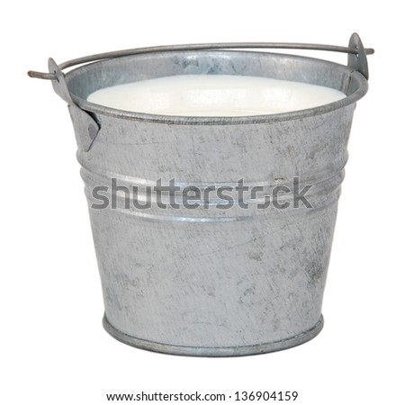 Milk in a miniature metal bucket, isolated on a white background - stock photo