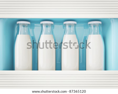 milk in glass bottle  stay in a refrigerator - stock photo