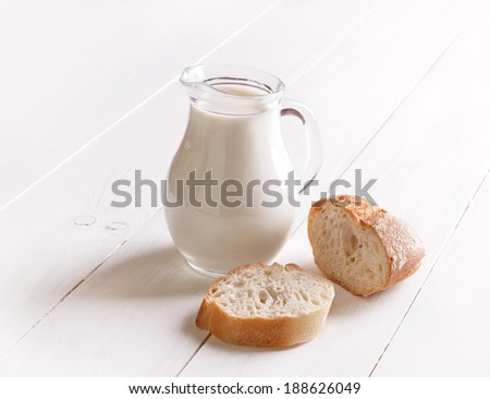 Milk in glass jug and bread on white wooden table