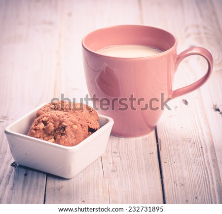 milk in pink cup with cookies on wood table,vintage tone style - stock photo