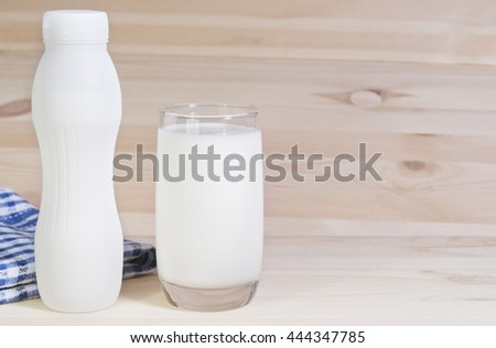 Milk in white plastic bottle and in glass on wooden background