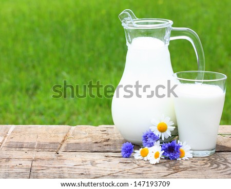 Milk jug and glass on wooden desk with chamomiles. - stock photo