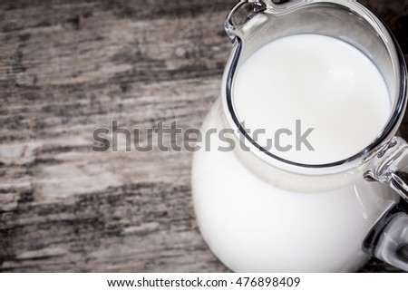 Milk jug full on wooden background, view from above, closeup.