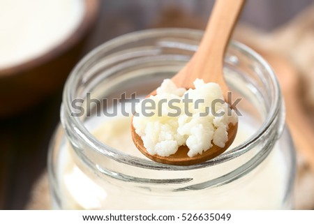 Milk kefir grains on wooden spoon on top of a jar of kefir, photographed with natural light (Selective Focus, Focus in the middle of the kefir grains)