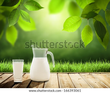 milk on table and sunny trees - stock photo