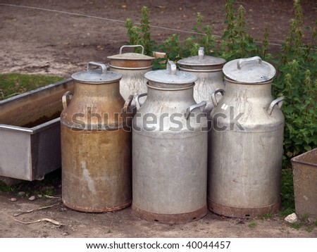 Milk organic traditional cans jugs in a dairy farm - stock photo