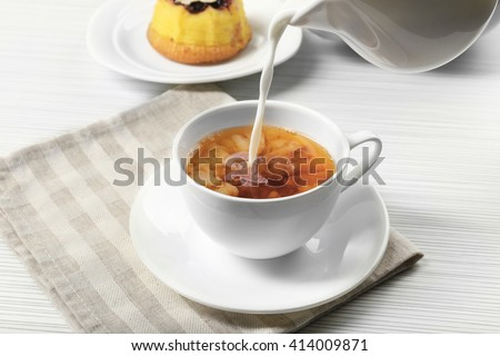 Milk poured into a cup of tea, close up - stock photo