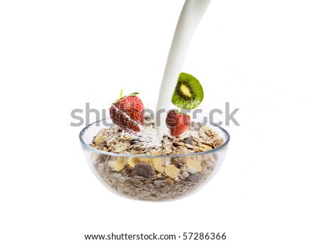 Milk poured into a glass bowl filled with muesli and fruits  on white - stock photo