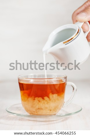 Milk poured into cup of tea by man hand
