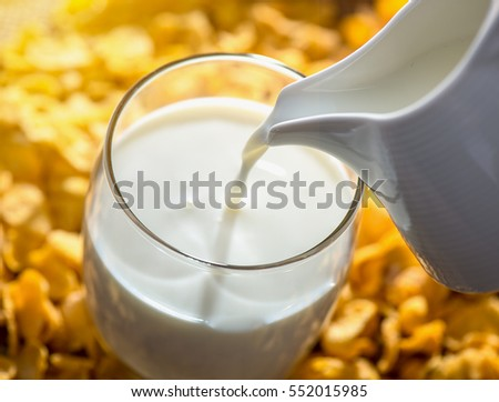 Milk pouring from a jug into a glass