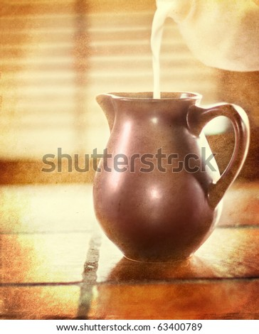 Milk pouring in a brown jug - picture in retro style - stock photo