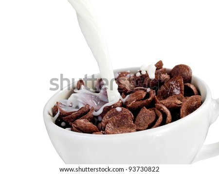 Milk pouring into a cup with chocolate cereal flakes - stock photo