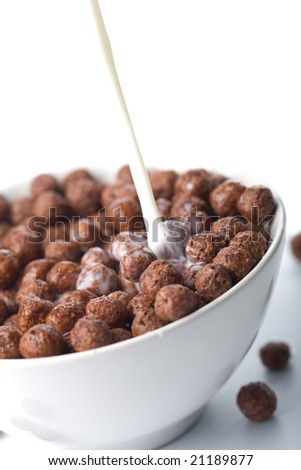milk pouring into bowl with chocolate balls isolated - stock photo