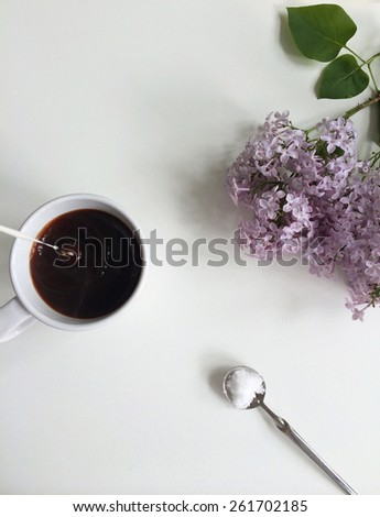 Milk pouring into coffee with sugar spoon and fresn lilac flowers - stock photo