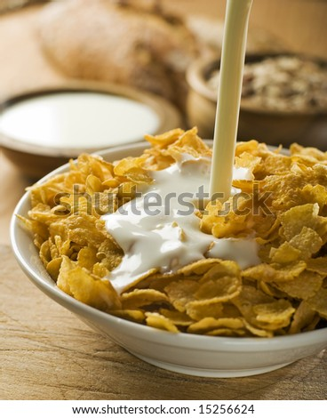 milk pouring on corn flakes in a bowl