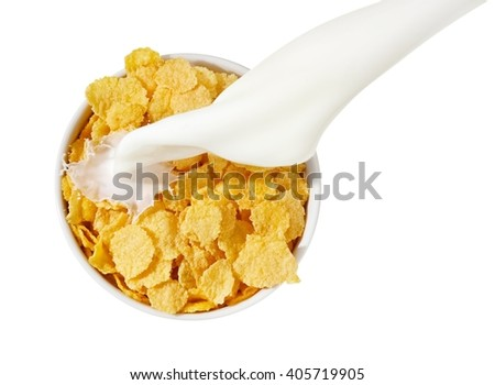 Milk pouring over a cup with cornflake, top view - stock photo