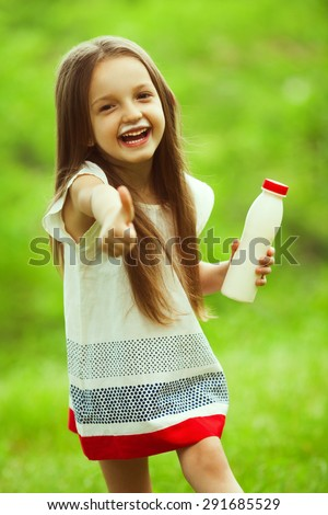 Milk products concept. Baby girl with long brown hair in white vintage summer dress drinking yogurt in the park, holding white plastic bottle, showing thumb up. Milk moustache under nose. Outdoor shot - stock photo