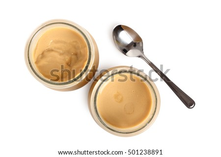 Milk pudding dessert in jars with spoon. Isolated with clipping path. Directly Above.