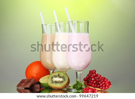 Milk shakes with fruits and chocolate on green background