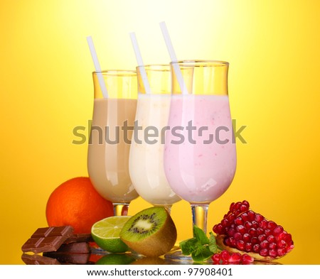 Milk shakes with fruits and chocolate on yellow background - stock photo