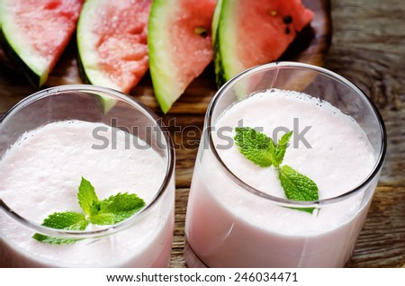 milk smoothie with watermelon on a dark wood background. tinting. selective focus