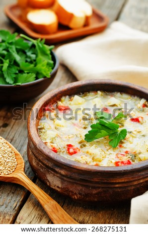 milk soup with potatoes, quinoa and peppers on a dark wood background ...