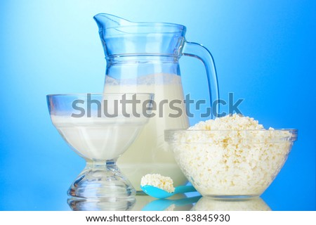 Milk, sour cream and cottage cheese on blue background