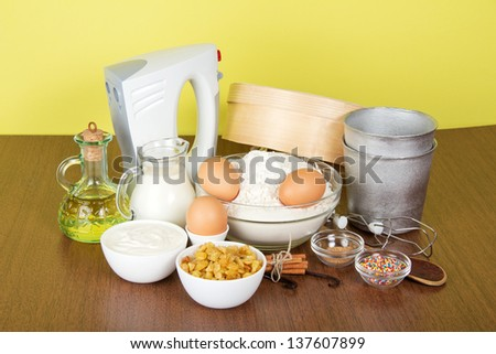 Milk, sour cream, flour, raisin and spices for an Easter cake, on a yellow background