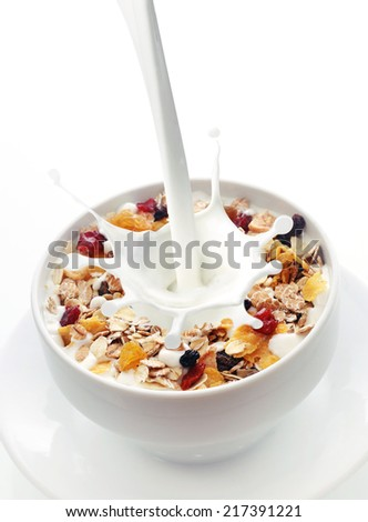 Milk splashing into a bowl of fresh muesli with a mix of wheat, oats and bran with dried fruit and nuts over white with copyspace - stock photo