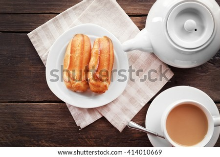 Milk tea with eclairs on wooden background. - stock photo
