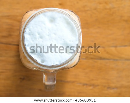 Milk tea with ice in Glass on wooden table,Top view focus.