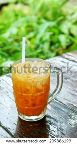 Milk tea with ice on wooden table (Thai beverage) - stock photo