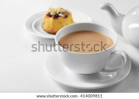 Milk tea with tea pot and a dessert on white background - stock photo