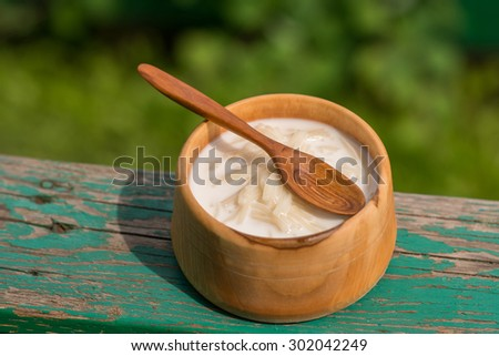 milk vermicelli in a handmade wooden bowl with handcarved wooden spoon outdoors - stock photo