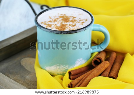 Milk with cinnamon on wooden table - stock photo