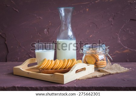 Milk with sandwich cracker on brown stone table over stone grunge background. - stock photo